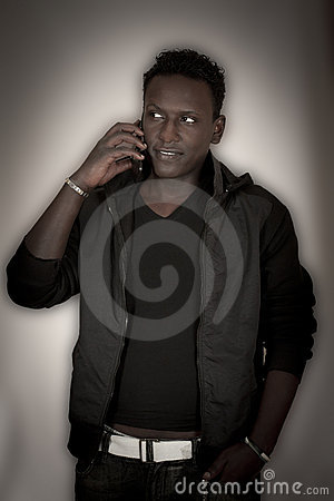 The dark-skinned young man with a mobile phone