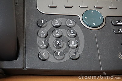 dark telephone dial buttons of the land line phone with numbers and letters together with a speed dial above them