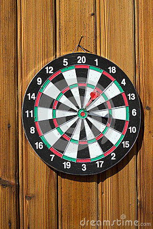 Dartboard on wood wall (dart hit target)