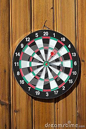 Dartboard on wood wall (dart hit target)