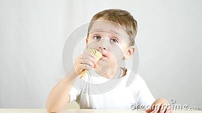 Das Kind isst Eiscreme in einem Waffelkegel und sitzt an einem Tisch Der Junge genießt einen köstlichen Nachtisch stock footage