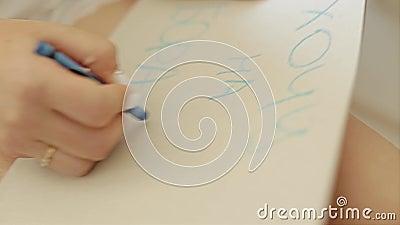 Das Mädchen schreibt in Bleistift auf ein Blatt der Pappe Shownahaufnahme der Hand des Mädchens Die Kommunion der Freundschaft stock video