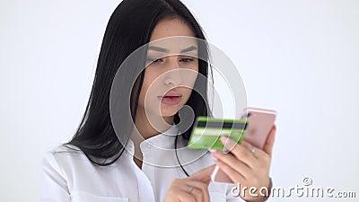 Das Mädchen wählt in der Telefondatenkarte Plastikkarte Shopaholic zahlt für den Kauf über das Internet stock footage