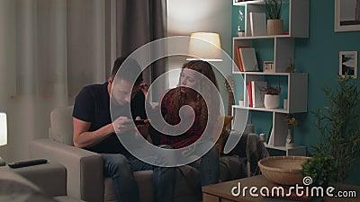 Das Verschieben des Mannes spielen im Spiel auf Smartphone und ignorieren seine Freundin stock video footage
