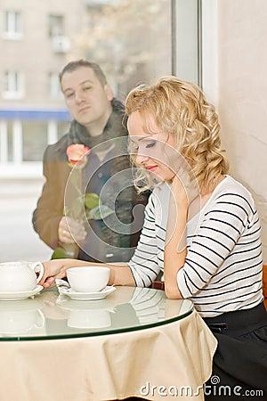 Data. Młoda kobieta czeka chłopaka przy małą kawiarnią