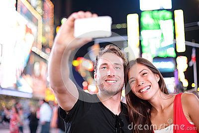 Datando os pares novos felizes no amor que toma a foto do selfie no Times Square, New York City na noite. Turista multirracial nov
