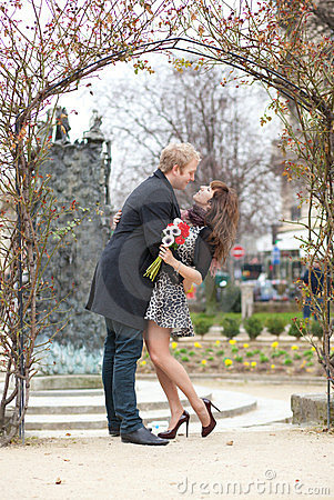 Dating couple hugging under an arch