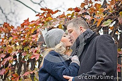 Datum. Jonge vrouw en man kussen openlucht. De herfst