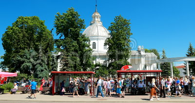 Daugavpils, Letland - 8 juni 2019: Mensen lopen op straat in de buurt van de katholieke kerk van Saint Peter in de ketting Stad stock footage