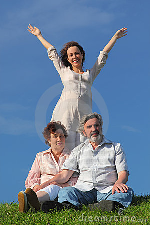 Daughter with apart hands, parents sitting on lawn Stock Photo