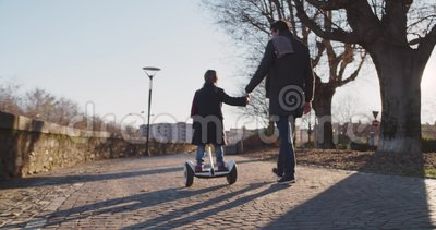 Daughter child girl learning segway riding with dad teaching in city.Modern future transport technology.Active safety. Family.Sidewalk urban outdoor.Warm sunset stock video footage