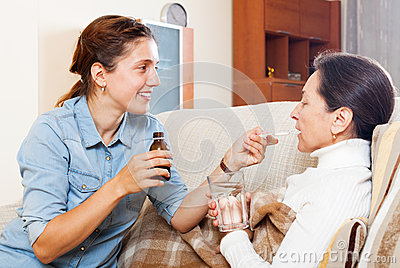 Daughter giving the liquid medicament to mature woman