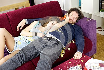 Daughter hugging father on couch sleeping with chaos around
