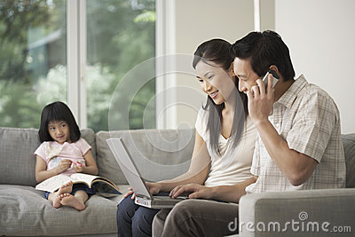 Daughter Looking At Couple Use Laptop And Cellphone