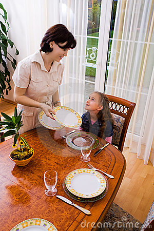 Daughter and mom setting the table