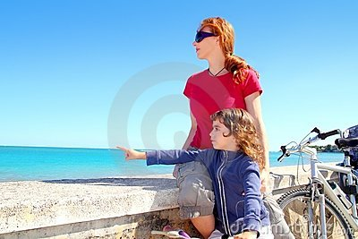 Daughter and mother on bicycle in beach