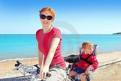 Daughter and mother on bicycle in beach sea