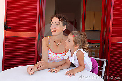 Daughter and mother sit on verandah round table