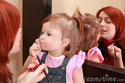 Daughter powders, mother makes make-up near mirror