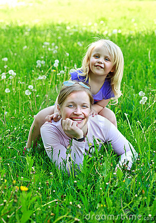Daughter sits on mother on a grass outdoors