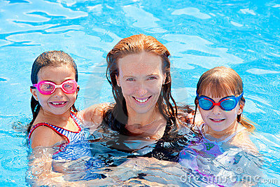 Daughters and mother family swimming in pool
