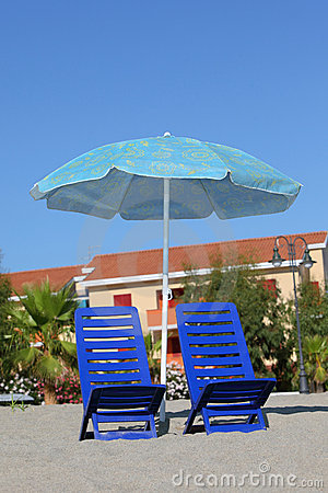 In day-time on sand chairs cost under umbrella