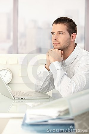 Daydreaming businessman sitting at desk