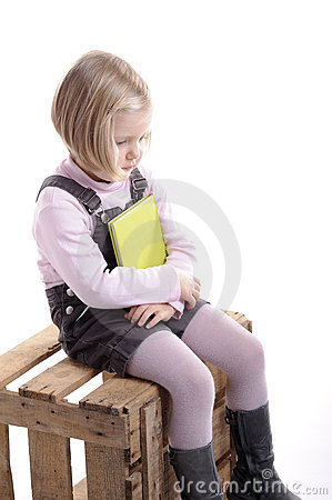 Daydreaming little blond girl with book