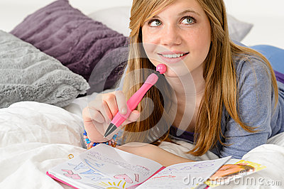 Daydreaming teenager girl writing her journal