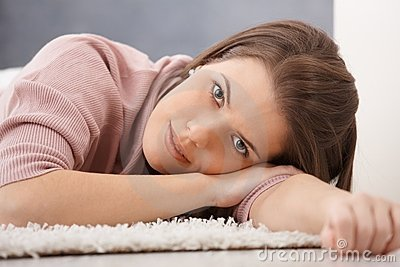 Daydreaming young woman on floor