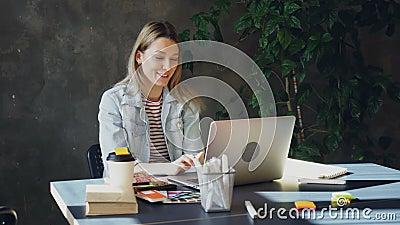 De aantrekkelijke jonge vrouw spreekt op skype op laptop terwijl het zitten bij lijst in modern bureau Zij spreekt stock video