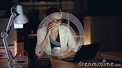 De aantrekkelijke vrouwelijke ondernemer spreekt op mobiele telefoon en gebruikt laptop die in bureau laat bij nacht werken moder stock footage