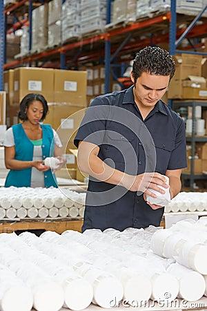 De arbeider die van de fabriek goederen controleren op lopende band