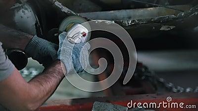 De arbeider in glazen maalt de besnoeiing op de rug van de auto De dienst van de autoreparatie Ontspruitende Vonken stock video