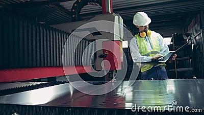 De arbeider van de fabriek observeert een lasermechanisme dat metaal verwerkt stock videobeelden