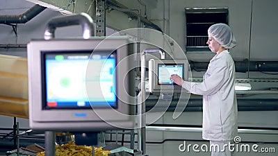 De arbeider van de voedselinstallatie controleert een transportband, volledig van chips stock videobeelden