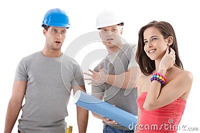 De arbeiders die van de contractant bij mooi meisje staren
