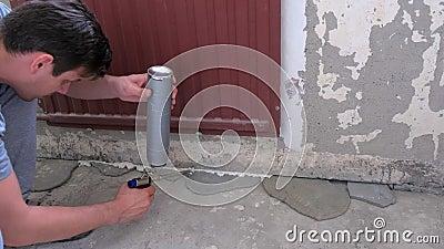 De arbeiders vullen barst tussen muur en cementvloer met ophangschuim in ruimte stock videobeelden