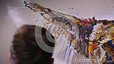 De artistieke ontwerper trekt een arend op de muur Schrift voor ambachtslieden schildert een afbeelding met acryloliekleur Schild stock videobeelden