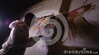 De artistieke ontwerper trekt een arend op de muur Schrift voor ambachtslieden schildert een afbeelding met acryloliekleur Schild stock video
