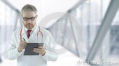 De arts voltooit de digitale checklist in de tablet-pc, die is opgenomen op de rode camera stock footage