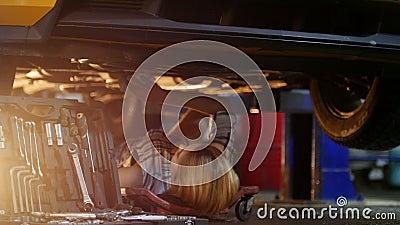De auto dienst Werktuigkundige die binnen de auto werkt Het jonge vrouw liggen onder de auto en veegt het met een vod af stock footage