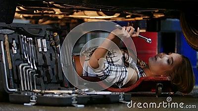 De auto dienst Werktuigkundige die binnen de auto werkt Het jonge vrouw liggen onder de auto, neemt een moersleutel en blijft wer stock videobeelden