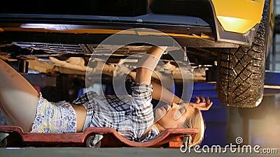 De auto dienst Werktuigkundige die binnen de auto werkt mechanisch meisje in kleine borrels die onder de auto liggen en het beves stock footage