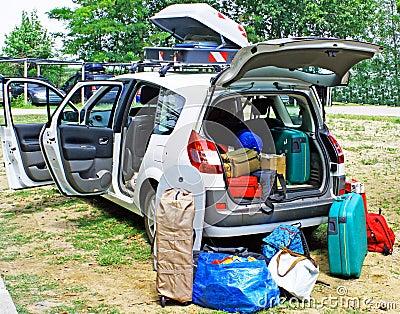 De auto van de familie die met bagage op vakantie wordt geladen