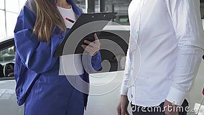 De autodienst, reparatie, overeenkomst en mensenconcept - niet erkende werktuigkundige en klant of autoeigenaar die document het  stock video