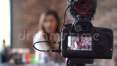 De Aziatische video van de vrouwenopname over schoonheidsmiddelen met DSLR op driepoot stock videobeelden