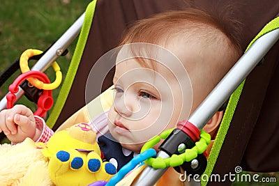 De baby in Wandelwagen staart