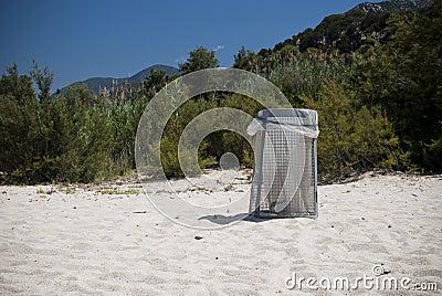 De bak van het huisvuil op een strand