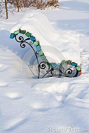 De bank van de winter die met sneeuw wordt behandeld